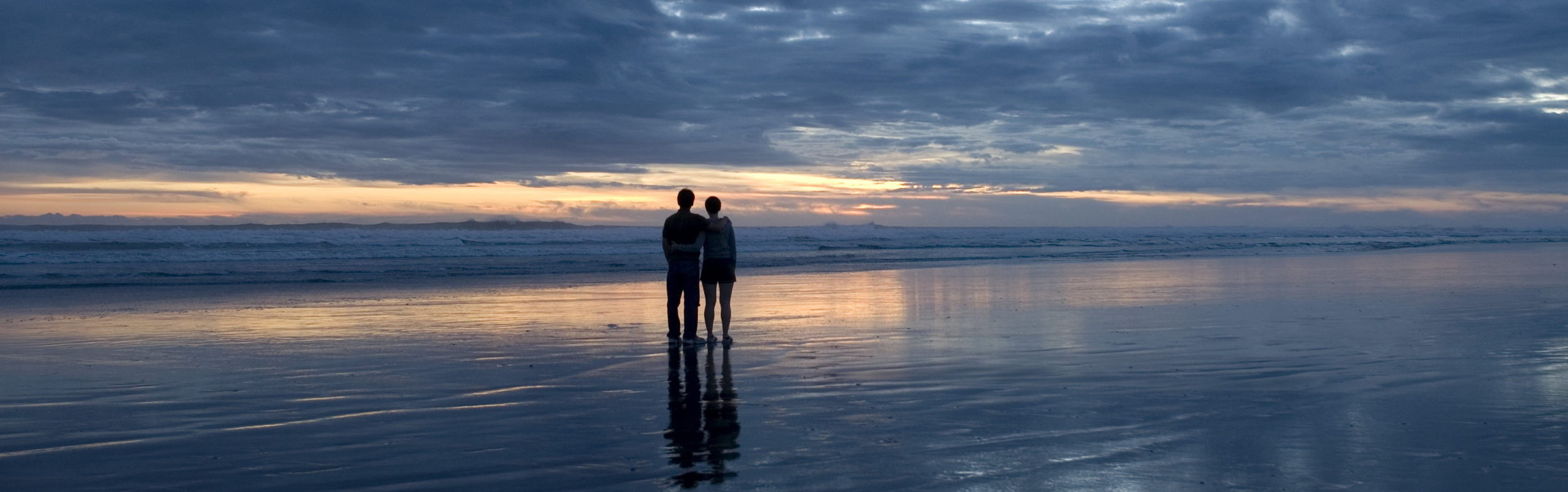 Two people on beach after sunset